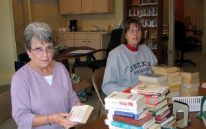 Volunteers sort books in preparation for shelving